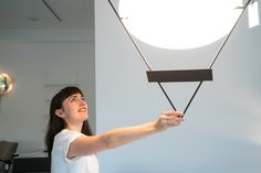 Sophie Pearce showing off the details of a Mario Botta light for Artemide