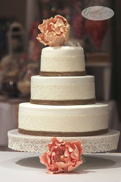 White vintage, lace, twine wedding cake with peach and apricot peonies