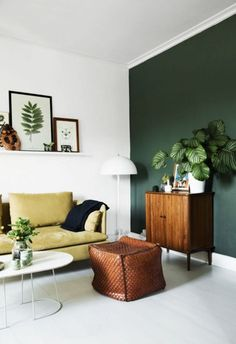 Yellow and green are a winning combo | dark green statement wall | retro sideboard | Yellow IKEA Söderhamn sofa is paired with a leather pouf and a simple white coffee table | For a luxe update - update your IKEA sofa with a Bemz cover in one of our 250+ fabrics