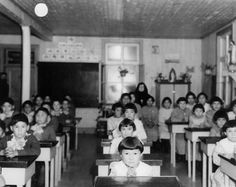 If you carefully examine the picture, you'll be see that all the children have their hands closed together, the girls all have the same haircuts and no child seems genuinely happy in the photo. The last thing you will notice is that a nun sits in the back of the class as if she is watching the children with keen eyes. This picture represents the marginalization of individuality and self-expression in the residential school system.