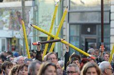 Un grupo de manifestantes sostiene lápices gigantes en los que se lee...#JeSuisCharlie