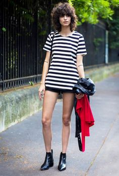 A striped t-shirt is worn with black shorts, ankle boots, and a leather jacket