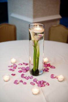 Simple wedding centerpieces of Picasso Calla Lilies, floating candle, votives, and Cool Water rose petals | by Dorothy McDaniel's Flower Market; Simple Color Photography