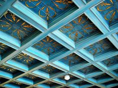 Blue painted ceiling with gold design within beams.