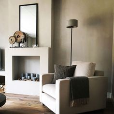 i like the accent chair and the throw, as well as the mirror above the fake fireplace