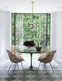 Dining space with ion pivot doors, woven chairs, and zinc tulip table.