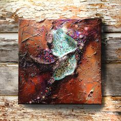 This unusual mixed media acrylic and jewel canvas painting is titled Cosmic Flower. This piece has thick layers of paint in a variety of colors. I used