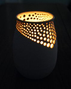 This beautiful ceramic luminary was wheel thrown and hand drilled in my home studio. The inside has been glazed in a clear glaze and the outside has been left as the raw clay surface, giving it a natural, organic feel. When lit from the inside with a candle, the asymmetric pattern