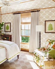 """Cowtan & Tout's Bamboo wallpaper is heightened by applied bamboo trim that frames a guest bedroom and extends onto the ceiling. Matouk bed linens and curtains in Norbar's Ozone add the """"luxury of white,"""" McMakin says. Floor lamp, Jamie Young. Cassard bookcase, Starbay. Carpet, Comeran. Lee Jofa's Polynesia adds a touch of the exotic to the armchair."""