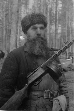 Armed with a PPSh-41 SMG, El Barykin, chief of the Gomel partisans, poses for the camera somewhere in the deep woods, home of all Russian partisans during the war, 1943.