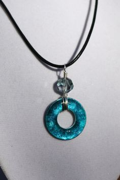 Real washer inked with blue and purple alcohol inks, sealed with resin, then wire wrapped with faceted crystal bead, hanging from 18 inch