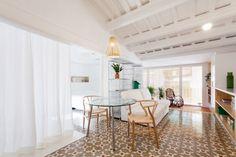 Estantes e cortinas substituem paredes neste apartamento em Barcelona