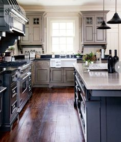 """""""The kitchen's colour scheme contributes to its 19th-century flavour...the couple used a deep charcoal shade that makes the feature a focal point but doesn't overwhelm the green-toned kitchen cabinetry."""""""