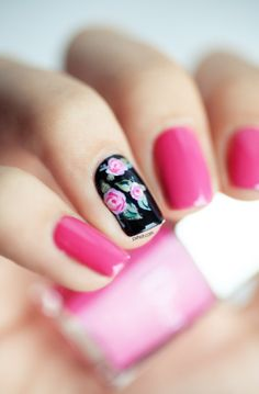Pink Dior nails with black floral pattern on ring finger