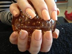 Acrylic nails with orange gel polish and Swarovski crystals on ring finger