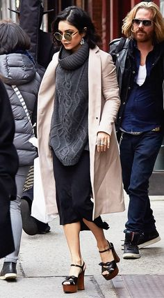 Vanessa Hudgens in a taupe coat, grey sweater, black skirt, black platforms, and sunglasses
