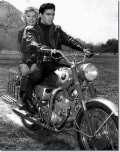 """Elvis Presley and Barbara Stanwyck on the set of """"Roustabout"""" in Thousand Oaks, Calif., Miss Stanwyck and Elvis are shown in a cow pasture where the film company was on location, March Elvis Presley, Estilo Cafe Racer, Barbara Stanwyck, Graceland, Vintage Motorcycles, Rock N Roll, Movie Stars, Harley Davidson, King"""