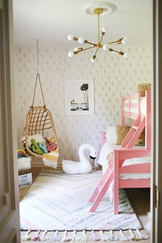 Love the natural hanging chair in the corner of this girl's room. So cute with the pink bunk beds.