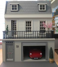 love this more modern, yet classic & timeless dollhouse. also love the car in the garage, the cherry tree on the balcony & the house numbers!!