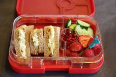 Egg Salad Sandwich packed in a Yumbox Panino with cucumbers, strawberries, and pomegranate seeds.  And our favorite Vacu Vin food pick to help pick up the strawberries!