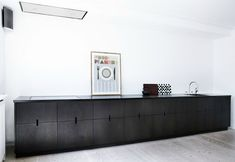 Super simple black kitchen with negative opening details.