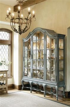Country blue cabinet, beautiful windows and gorgeous chandelier.