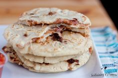 A stack of five pupusas with the filling showing.