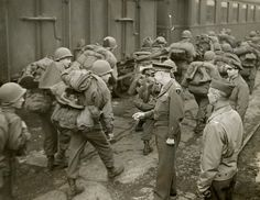 General Dwight Eisenhower greets GI's loaded down with full packs as they arrive at a French port. Feb. 25, 1945.