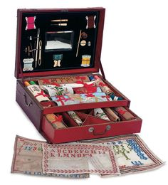 """Theriault's Antique Doll Auctions - French Child's Needlework Box with Samplers - 15"""" x 11"""". A wooden framed box is covered with faux-burgundy leather and decorated with rich silver mounts and corners. It hinges open to reveal two-layered interior containing a number of sewing and handwork tools and accessories along with 14 various canvas and linen needlework and alphabet samplers in various states of completion. Excellent condition. Circa 1890."""