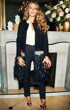 Blake Lively wears a button-down blouse, high-waisted pants, statement coat with feather detailing, a metallic clutch, and strappy Christian Louboutin heels