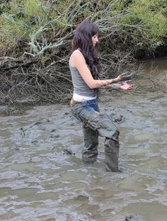 Muddy brunette in shorts and waders