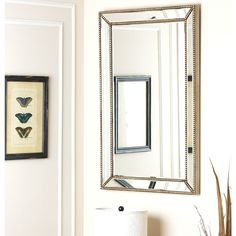 Make any room appear larger and brighter with the help of this Cosmo mirror. Crafted with a unique silver frame, this chic mirror is accented by nail head style borders to elevate the style in any bedroom, living room, entryway or hall.