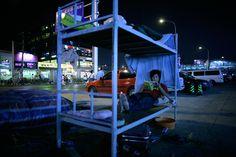 Um trabalhador chinês lê um livro enquanto estava deitado em uma cama em uma rua movimentada, tarde da noite em Pequim, domingo, 13 de julho, 2008. Noturna em Pequim revela uma cidade que está na moda e cosmopolita, embora muitas partes da cidade ainda mantém seu caráter tradicional. photoblog.nbcnews.com