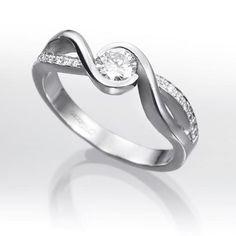 Anillo solitario de diamantes CAPRI Sortija de oro blanco 18 kts. tipo solitario montada con un diamante central talla brillante calidad G-VS engastado en bisel cincelado, con línea de diamantes talla brillante en grano con 0,15 quilates de peso total.