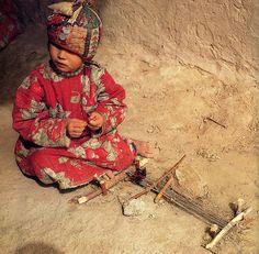 learning to weave on a toy loom | Turkmenistan, Central Asia | Dr. Jon Thompson | Carpet Magic: The art of carpets from the tents, cottages and workshops of Asia | UK: Barbican Art Gallery | 1983