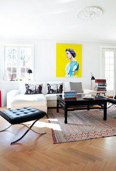 Stuen er indrettet med enkle møbler i sorte og hvide nuancer. De lader kunsten på væggene tale, klæder rummet med den velholdte lakerede sildeparket, og så kan de tåle at blive brugt. Over sofaen pynter et knaldgult maleri af Cathrine Raben. Tæppet under sofabordet er antikt, læselampen er fra Bestlite. Ikea-sofaen er kombineret med fodskamlen der tilhører den klassiske Barcelona-stol.