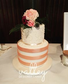 Rose gold is on trend at the moment. This ivory iced cake with rose gold stripes and ivory stencilling was beautiful, complemented with fresh flowers