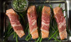Stek laksefilet rullet i tynne skiver spekeskinke i ovnen og server med kokte aspargesbønner og urtedressing.