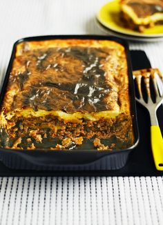 Classic moussaka - layers of minced lamb, potato and aubergine, covered in white sauce and baked to make the classic Greek dish moussaka.