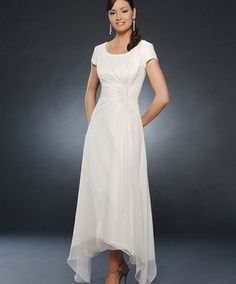 7834 - Special Occasions - Collections | Bonny Bridal 7834 Short cap sleeve gown has a scoop neckline. Shirring drapes asymmetrically across the bodice into beaded and embroidered accents. The skirt falls into a T-length cruved hem that's longer along the sides. Fabrics: Chiffon