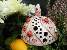 Kopeček se srdíčky Keramický kopeček s domečkem posázen srdíčky a květy,glazovaný, použita engoba. Možno použít jako svícínek. Výška 120mm Průměr 140mm