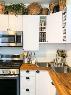 Baskets above white kitchen cabinets, organized spice rack, butcher block countertops Farmhouse Kitchen Decor, Kitchen Redo, Home Decor Kitchen, Home Kitchens, Kitchen Plants, Kitchen Ideas, Kitchen Baskets, Kitchen Makeovers, Custom Kitchens