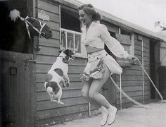 A circus (or perhaps rodeo) performer and a lively little dog jump rope together in this delightful vintage snapshot.