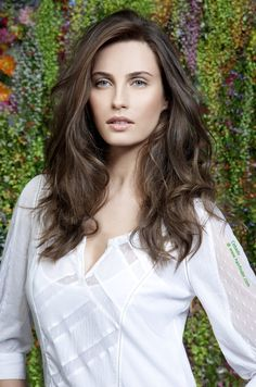 A great way to show off your long hair and still look elegant is to move the part from the center a bit to the side to create a slight asymmetry and to either use the natural curl in the hair to form large waves for motion and volume throughout. Long layers keep the weight balanced and also aid with the generation of some volume in the lower areas. Blow dry with the hair over the head to get that chic lift on the roots and soft flow. Collection: Women 2011 Hair: Cebado