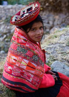 South America | Portrait of a Quechua girl wearing traditional clothes, headdress and shawl, Peru