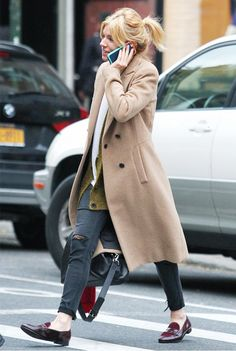 Sienna Miller wears a cardigan with a camel coat, skinny jeans, and loafers