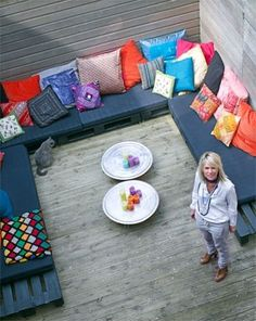 a colorfully cozy outdoor deck using pallets for seating
