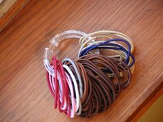 Use a cheap dollar store shower curtain ring to keep hair ties organized :O)