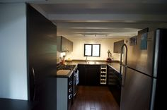 """Full-sized stove and full-sized refrigerator in """"hOMe"""" the 221 sq ft tiny house on wheels  designed by Andrew Morrison and Gabriella Morrison of TinyHouseBuild.com. Bathroom at one end, kitchen at the other end, stairs with built-in storage in the middle."""
