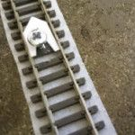 How To Lay and Fix Track: Insertinga small screw or drawing pin between the sleepers of alternate track sections to temporarily fix it in place and prove alignment can save hours of work.  Read the full article for more track tips.